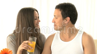 Woman kissing her boyfriend and drinking orange juice Stock Photo