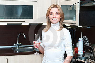 Woman in kitchen with champagne