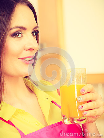 Woman in kitchen drinking fresh orange juice Stock Photo