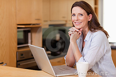 Woman in the kitchen with her laptop