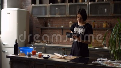 Woman in kitchen looking at recipe on tablet pc stock video