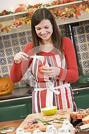 Woman in kitchen making Halloween treat