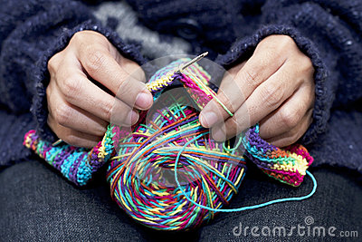 Woman knitting with collorful wool.
