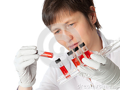 Woman in lab coat with  liquid samples.