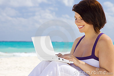 Woman with laptop computer on the beach