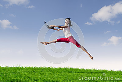 Woman with laptop jumping in meadow