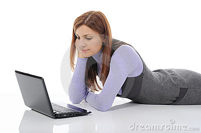 Woman with laptop lying on the floor