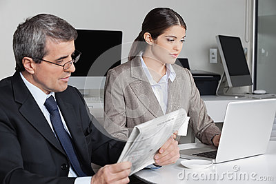 Woman with laptop and man reading