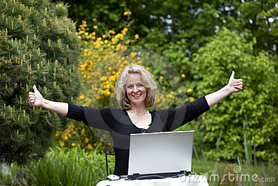 Woman with laptop posing both thumbs up