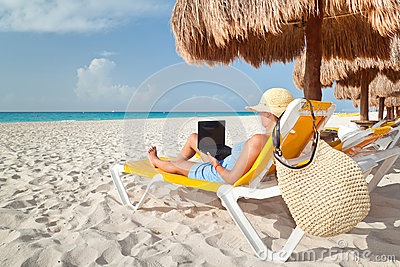 Woman with laptop relaxing on the deckchair