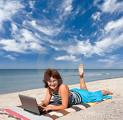 Woman with laptop at sea beach