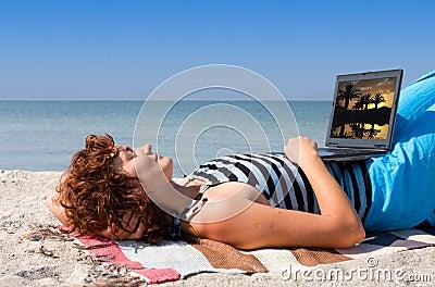 Woman with laptop sleep at sea coast