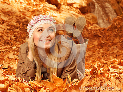 Woman lay down on autumnal foliage