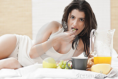 Woman laying on bed and having breakfast
