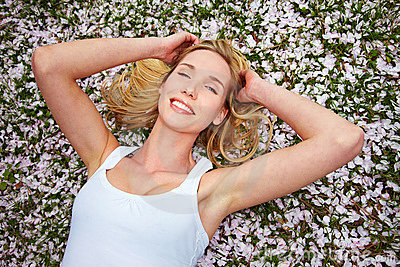Woman laying on cherry blossoms