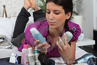 Woman laying with cosmetic products
