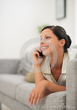 Woman laying on couch and speaking cell phone