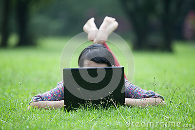 Woman laying on grass using laptop
