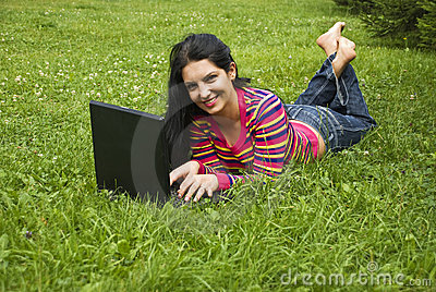 Woman laying in green grass and working on laptop