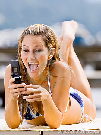 Woman laying on pier text messaging