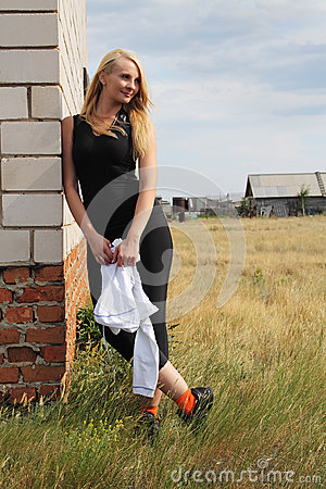 Woman lean on house brick wall.