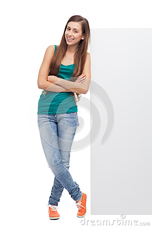 Woman leaning against blank billboard