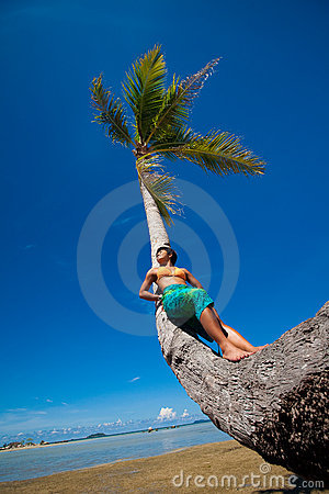 Woman leaning against coconut tree by a tropical b