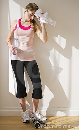 Woman leaning against wall after workout