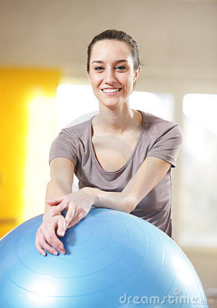 woman leaning on an exercise ball at the gym