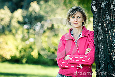 Woman leaning on the tree stem
