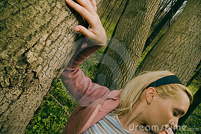 Woman leaning on tree trunk.