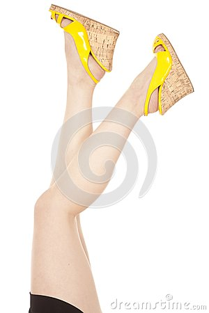 Woman legs apart yellow shoes