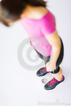 Woman legs standing on scales