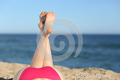 Woman legs sunbathing on the beach lying down