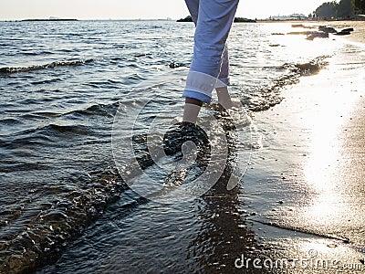 Woman legs walking along the sea coast