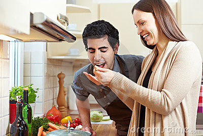 Woman letting man taste a soup