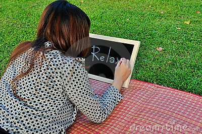 Woman lie down on grass and write on blackboard