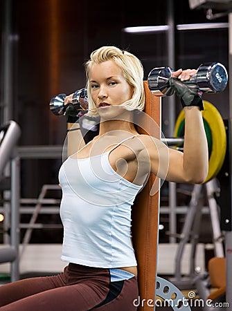 Woman lifting heavy dumbbells