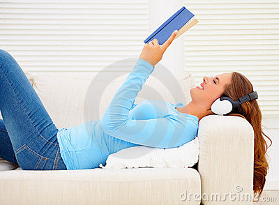 Woman listening to music while reading a novel