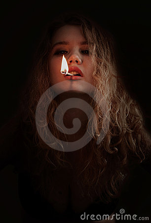 Woman with lit match in mouth