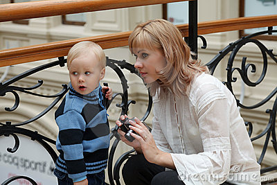 Woman and little boy against forged fencing