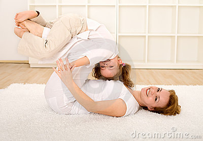 Woman and little girl having fun on the floor