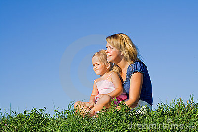 Woman and little girl outdoors sitting