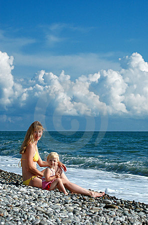Woman and little girl sit on seacoast
