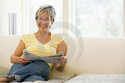 Woman in living room reading newspaper smiling
