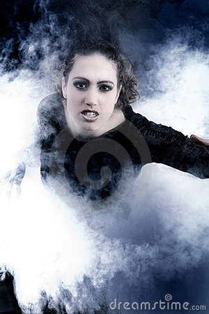 Woman with long curly hair crawling out of smoke