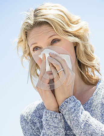 Woman Looking Away While Blowing Nose Against Clear Sky
