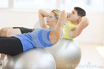 Woman Looking Away While Exercising On Fitness Ball At Gym