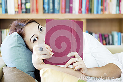 Woman looking from behind book
