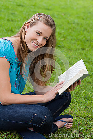 Woman looking at the camera while holding a book